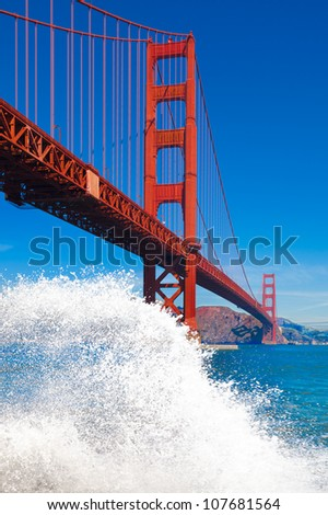 Golden Gate Bridge in San Francisco with big wave splash and spray in the foreground - stock photo