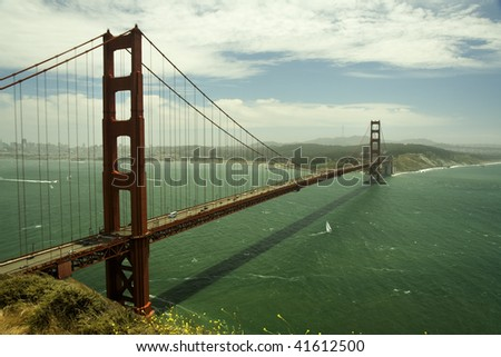 Golden Gate Bridge over San Francisco Bay with green ocean and blue skies with clouds