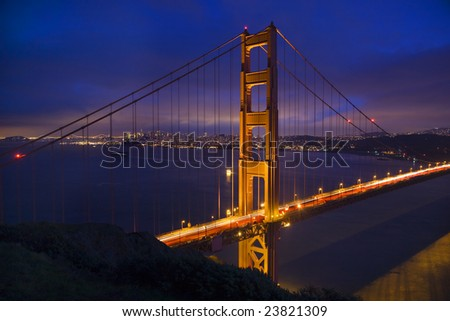Golden Gate Bridge Tall Evening with Lights of San Francisco California in background