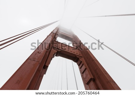 Golden Gate bridge tower emerging from iconic San Francisco bay fog bank.