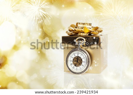Golden gift box and clock close to midnight on sparkling holiday background