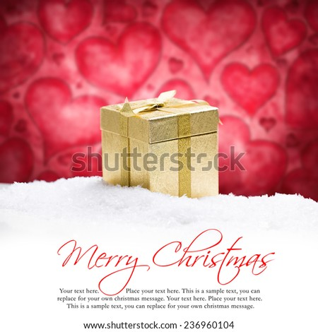 golden gift box in the snow in front of a heart background - stock photo