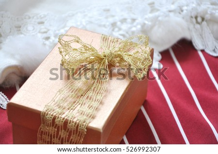 Golden gift box on red and white stripe background