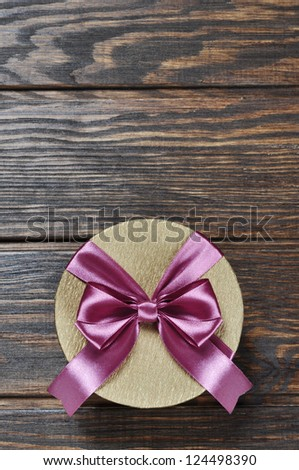 Golden gift box with pink ribbon over wooden background - stock photo