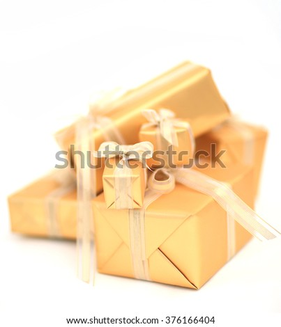 Golden gift boxes with golden ribbon on whiter background.