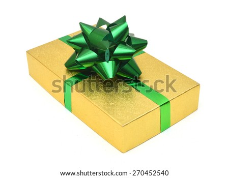 Golden gift wrapped present with green ribbon bow isolated on white - stock photo