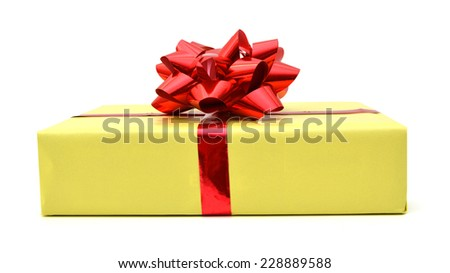 Golden gift wrapped present with red ribbon bow isolated on white  - stock photo