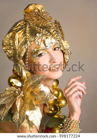 Golden girl. Young woman posing in holiday artistic image with New Year decoration.