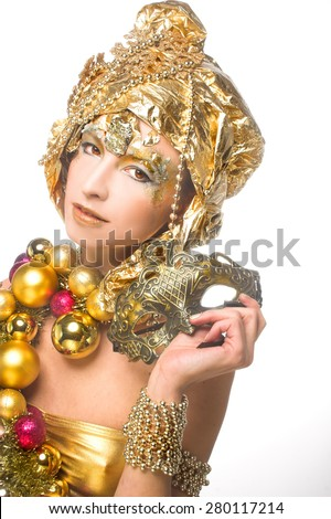 Golden girl. Young woman posing in New year image with holiday  decoration and mask. - stock photo