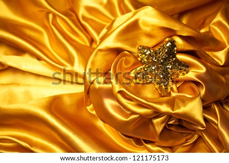Golden glamour theme with sparkling christmas star on wavy golden atlas (satin) background. Copy-space. Studio shot