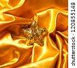 Golden glamour theme with sparkling christmas star on wavy golden atlas (satin) background. Studio shot - stock photo