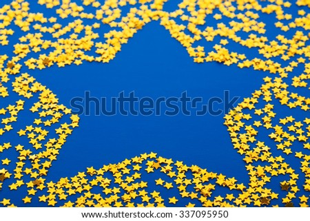 Golden glittering star shaped Christmas ornament isolated on blue background  - stock photo