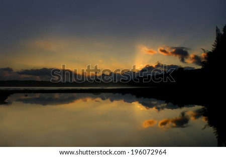 Golden glow of sunrise reflects on the surface of a bay on the island of Kauai.  Mist rises and clouds are tinged with pink.             - stock photo