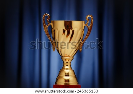 Golden glowing trophy cup on a dark blue background - stock photo