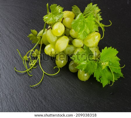 Golden grape cluster with leaves and  tendrils on a black slate board  - stock photo