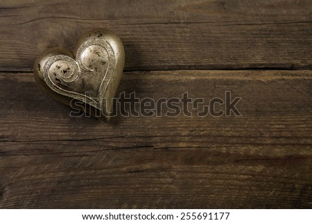 Golden heart on old wooden vintage background.