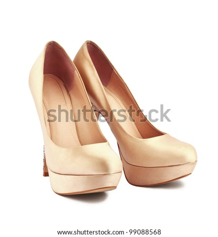 Golden high-heeled shoes over white background