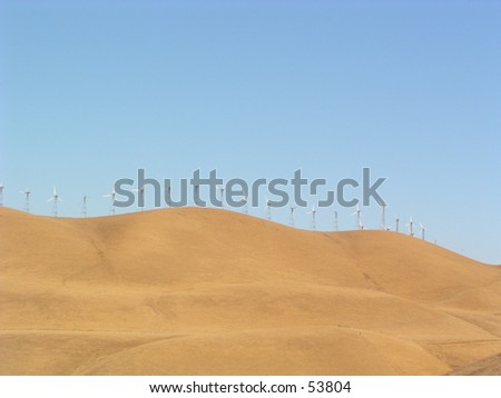 golden hills in california with windmills all over to generate electricity