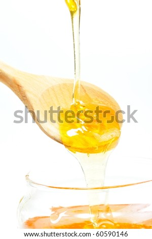 golden honey pouring from wooden spoon