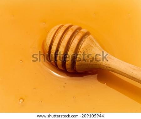 Golden honey  with wooden dipper. - stock photo