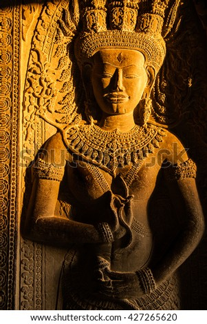 Golden hour light through windows at Apsara statue at Angkor Wat