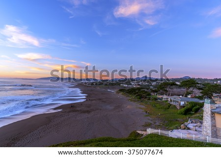 Golden hour, people on the beach, painted sky & sea, waves crashing at sunset on Moonstone Beach, next to Shamel Park, traveling the Big Sur Highway, on the California Central Coast, near Cambria CA. - stock photo