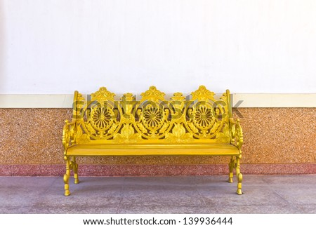 golden iron bench front of the white board - stock photo