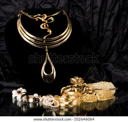 Golden jewelry on black background - stock photo