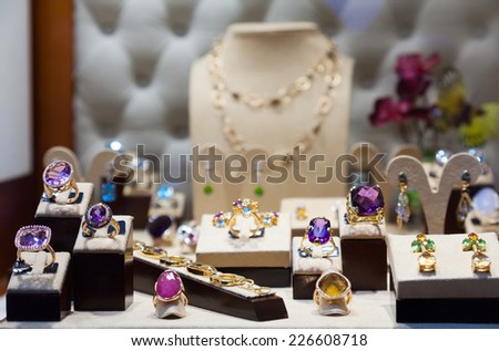 Golden jewelry with gems at showcase  - stock photo