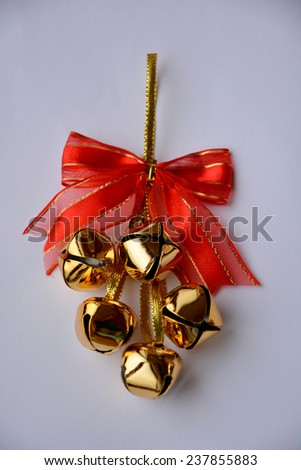 Golden jingle bells hanging on ribbon, with red bow, isolated on white background
