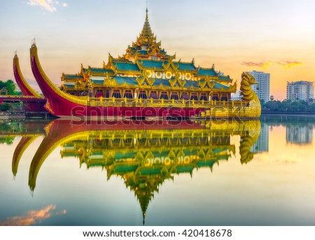 Golden Karaweik palace reflecting on Kandawgyi lake looks like an ancient royal barge. Sunset time. Yangon, Myanmar