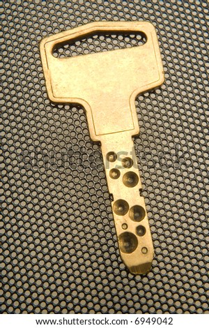 golden key from above over grid background - stock photo
