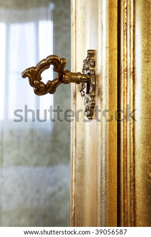 golden key in the door a rich furniture - stock photo