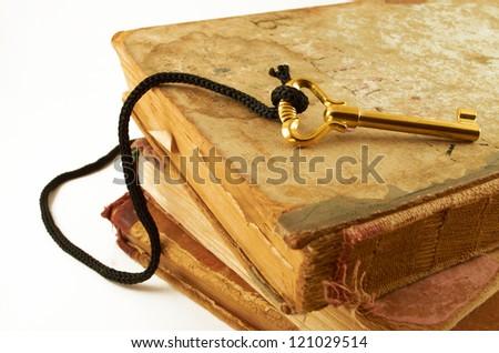 Golden key on old books isolated on white background - stock photo