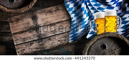 Golden lager, beer barrels and the Bavarian flag in a still life horizontal banner to celebrate the Oktoberfest in Munich in autumn, with copy space on rustic wood - stock photo
