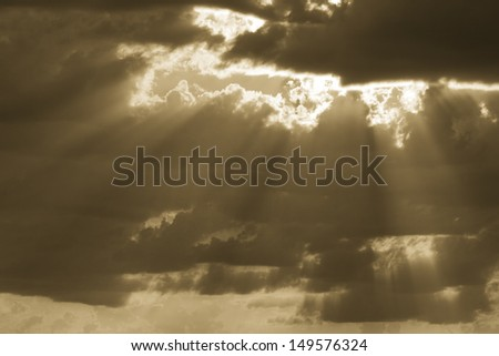 Golden light beams shine through the clouds on this warm, sunny morning. - stock photo