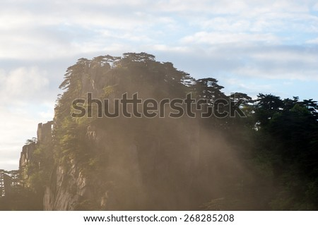 Golden light from the rising sun envelopes a granite peak in the Huangshan Mountains (Yellow Mountains), Anhui Province, China - stock photo