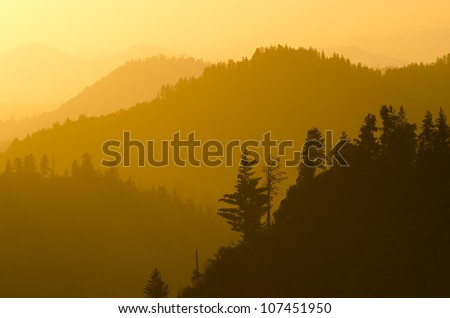 Golden light hitting the mountains as seen from Morro Rock in Sequoia National Forest. - stock photo