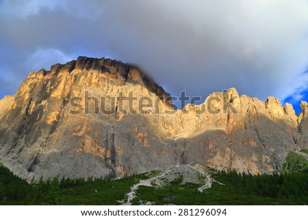 Golden light illuminates vertical walls of Sella massif, Dolomite Alps, Italy