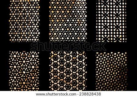 Golden light through carved window - stock photo