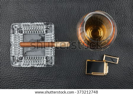 Golden lighter with a glass of alcohol and cigar lying on a black skin, can be used as background - stock photo