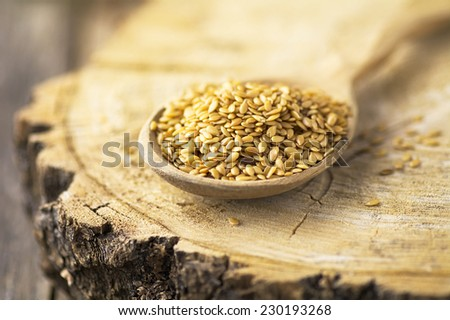 Golden linseed on wooden spoon, macro shot - stock photo