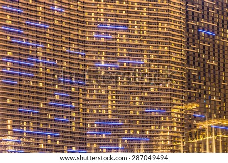 Golden lit modern high rise building with many windows - stock photo