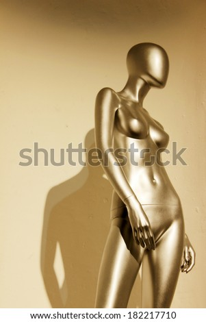 Golden mannequin in the form of a sexy woman - stock photo