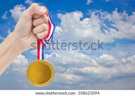 Golden medal in woman's hand with blue sky