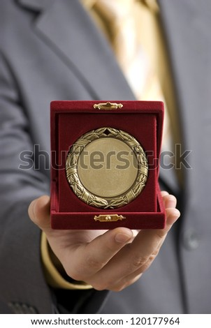 Golden medal offered as a symbol of success. - stock photo