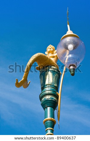 Golden mermaid street lamp with sky