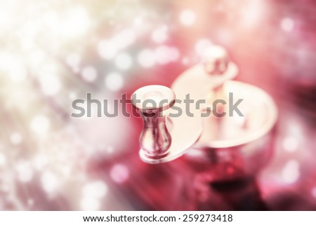 golden metal coffee-mill handle on a colorful abstract background with rays of light beaming from the left - stock photo
