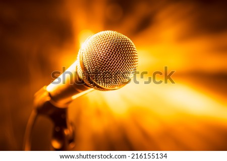 golden microphone on stage - stock photo