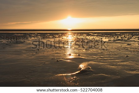 Golden natural sea sunset or sunrise reflection in nature with sun in clouds scenery and orange sky landscape.